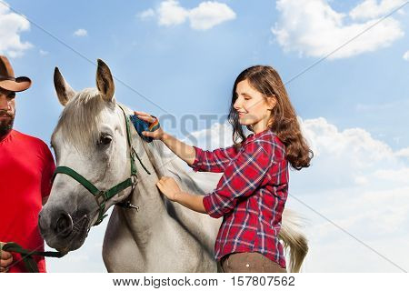 Happy young woman standing grooming the mane of her white horse with a brush while man in cowboy hat holding it by a bridle