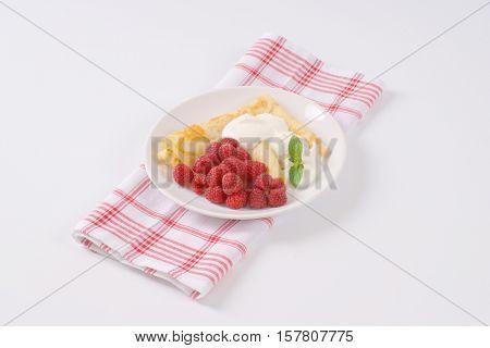 plate of pancakes with fresh raspberries on checkered dishtowel