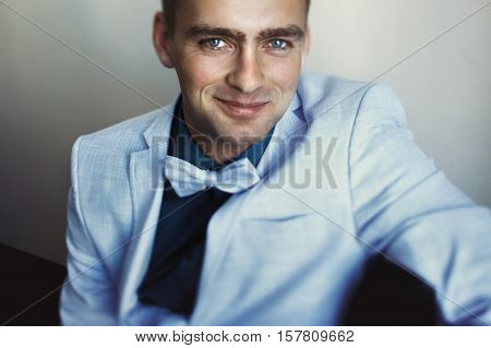 Fiance with blue eyes wearing blue suit with a bow tie