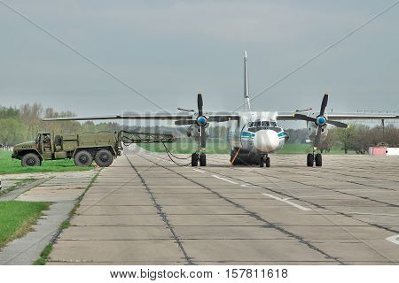 Vasilkov Ukraine - April 24 2012: Ukraine Air Force Antonov An-26 cargo plane is preparing to start the engines with the starter vehicle