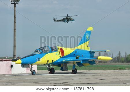 Vasilkov Ukraine - April 24 2012: Ukraine Air Force Aero L-39 Albatros parked on the apron of the airfield and Mil-Mi-24 attack helicopter landing on the runway on the background