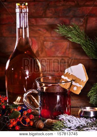 Still life of winter hot drink with bottle of red wine . Warming mulled wine with cookie in form of house on brick wall.