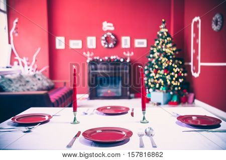Beautifully Laid New Year Table With Red Plates And Cutlery On A Background Of Decorated Room With C