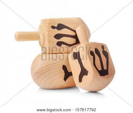 Wooden dreidels for Hanukkah on white background