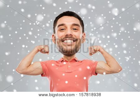 fitness, strength, sport, winter and people concept - happy smiling young man showing biceps power(funny cartoon style character with big head) over snow on gray background