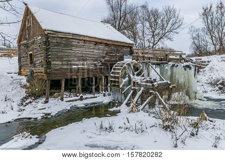 Old watermill in Krasnikovo, Kursk region. Winter, watermill is frozen in ice, covered with Icicles