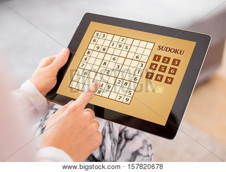 Woman playing Sudoku on tablet computer at home