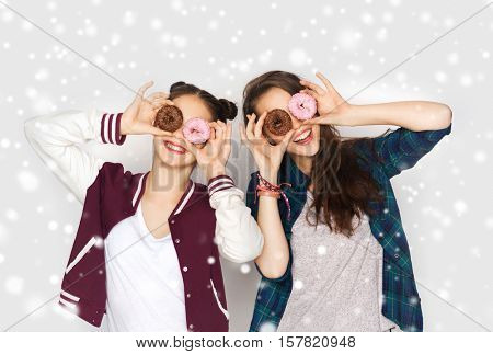 winter, christmas, people, holidays and fast food concept - happy smiling pretty teenage girls or friends with donuts making faces and having fun over gray background and snow
