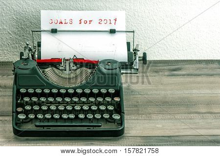 Typewriter with white paper page on wooden table. Goals for 2017. Vintage style toned picture.