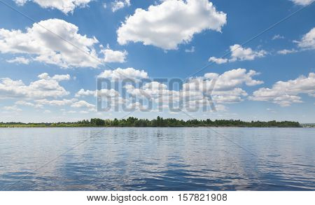 Panorama of shoreline and cloudscape reflected in calm river at sunny summer day