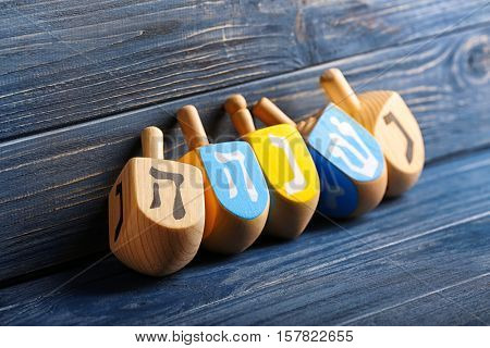 Dreidels for Hanukkah on wooden background