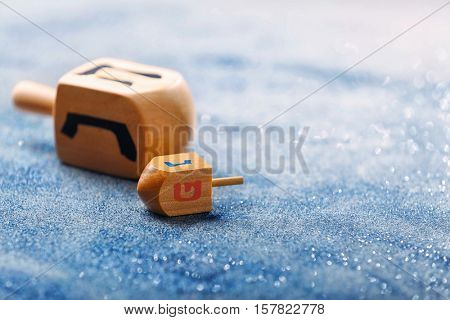 Wooden dreidels for Hanukkah on light sparkling background