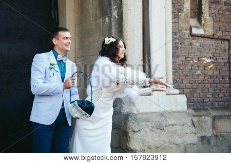 Bride throws sweets while fiance is holding a basket