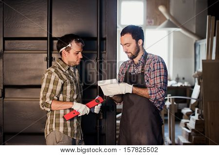 Happy male carpenter showing something to coworker ruler and notebook in workshop.