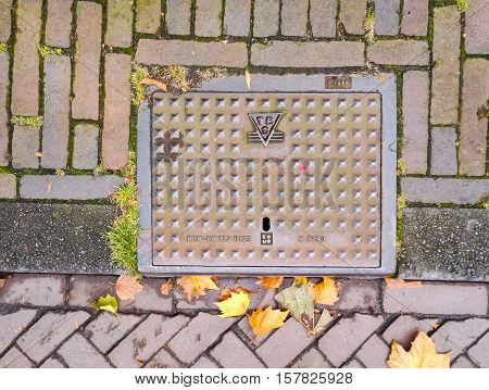 Amsterdam, Holland - 10 OCTOBER 2016: Manhole cover on the road of Amsterdam with patterns and inscriptions
