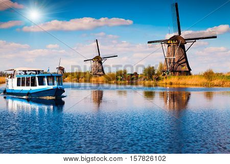 Walking boat on the famous Kinderdijk canal with windmills. Old Dutch village Kinderdijk UNESCO world heritage site. Netherlands Europe.