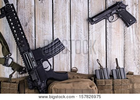 Modern assault riflegun and military belt with ammo on wooden table.Top view