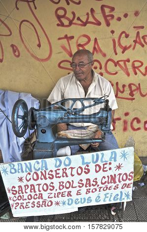 Man offers shoemaker services in the city of Aracaju, state of Sergipe, Brazil. May 22, 2009