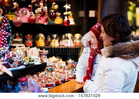 Mother and little girl in warm hat watching handmade glass Christmas tree ornaments and snow globes at traditional German Xmas street market. Family with child shopping for presents on winter fair.