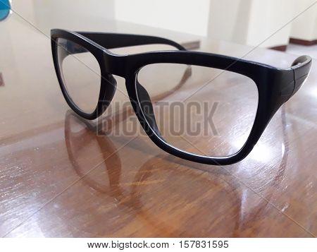 Ordinary glasses Above Brown Colored Glass Desk