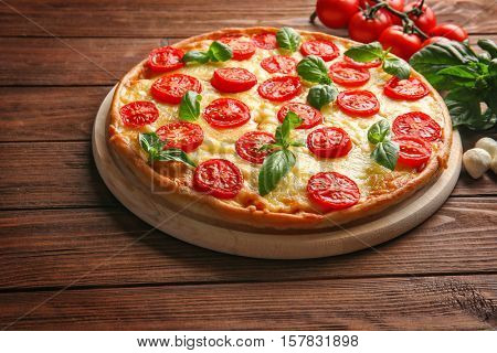Fresh tasty pizza Margarita and tomatoes on wooden background