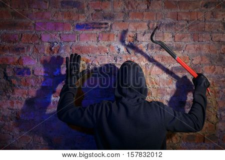Burglar standing with raised arms