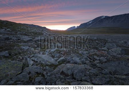 Bright colored striped sunset over the harsh rocky Sarek landscape