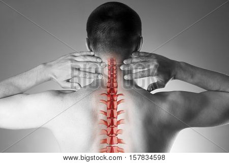 Spine pain man with backache and ache in the neck black and white photo with red backbone on gray background