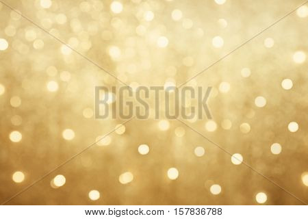 Golden beautiful blurred bokeh background with copy space. Holiday texture. Wallpaper. Glitter light spots on golden background defocused