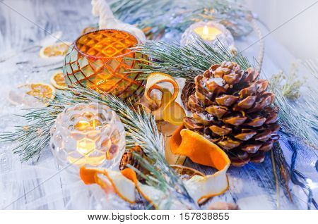 New year and Christmas winter decoration on rustic white wooden background with snow covered fir branches,  tangerines, cones, candlestick, candle and orange slices. Top view