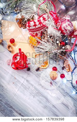 New year and Christmas winter decoration on rustic white wooden background with snow covered fir branches, tangerines, cones and shopping cart full of gifts. Copy space background