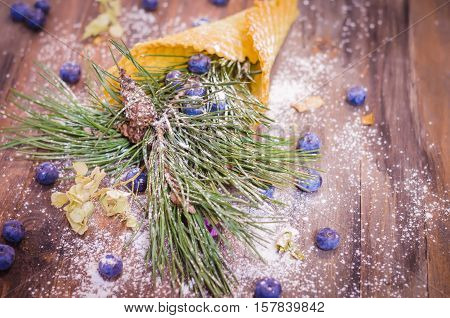 Festive scene with fir branches and blueberries in a powdered waffle cone on rustic wooden background, Copy space, vintage decoration