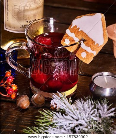 Close up of glass mug of warming smoking bishop drink with bottle of wine . Label on bottle of wine. Warming mulled wine with cookie in form of house on brick wall.