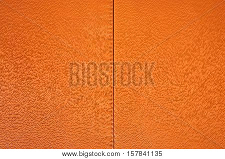 Orange leather texture. Leather stitched fabric stitched in the middle
