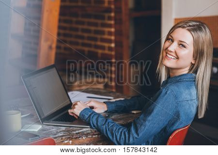 Portrait of an attractive young blonde woman looking over her shoulder while sitting at a table in her loft apartment using a laptop