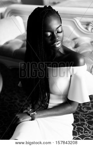 black and white photo of incredible african woman sitting on the floor in vip europian hotel. Hotel room with classic interior