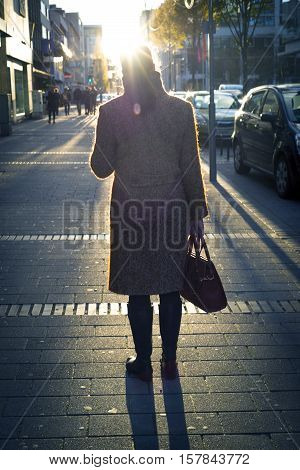 Women in Coat in Downtown Street with the Sun in the Front