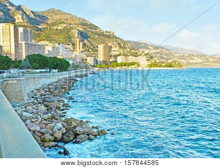 The Boulevard of Loui II is the seaside promenade of Monaco overlooking Monte Carlo high-rises greenery of Japanese garden and the green coast of Mediterranean sea.