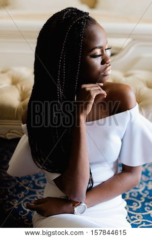 Photo of american black woman. Model sitting on the floor with hand on her face. Amazing luxury hotel