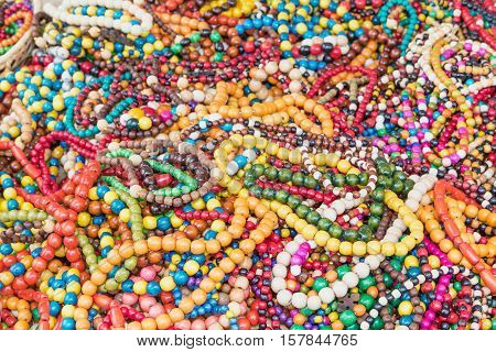 The pile of multicolored necklaces made of wooden beads of different sizes