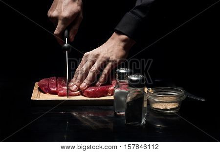 Best receipt. Close up of chefs hands chopping meat while working and cooking in restaurant.