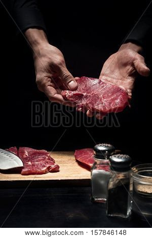 Good receipt. Close up of chefs hands holding meat while cooking and working in reastaurant.