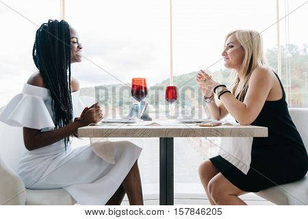 two beautiful women drinking alcohol in luxury restaurant in front of the big windows. African and europian women are chatting. African girl is in white, blonde girl is in black dress.