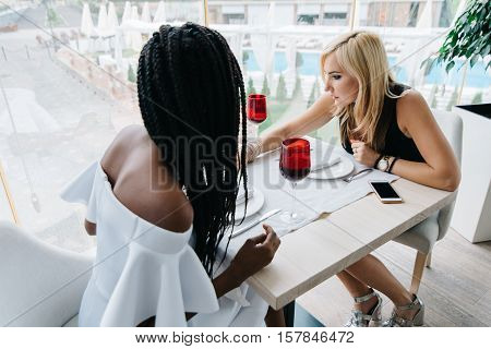 two beautiful women drinking alcohol in luxury restaurant. African and europian women are chatting. African girl is in white dress with bare shoulders, blonde girl is in black dress.