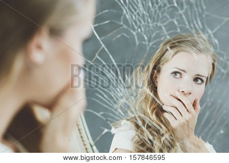 Girl with mental problem looking at herself in a mirror