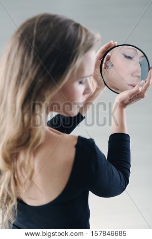 Teenager with complexes holding small broken mirror