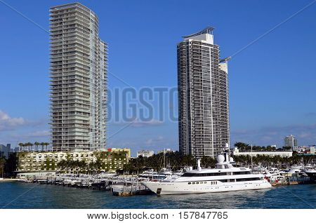 Luxury mega yacht moored at and luxury condo towers overlooking the Miami Beach Marina