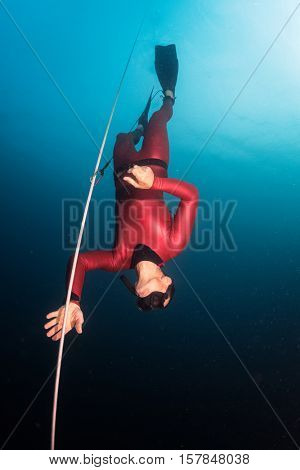 Free diver descending along the rope in the depth