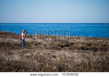 Young lady with backpack taking a picture in a field