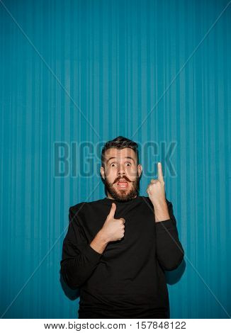 Portrait of young man with shocked facial expression pointing up over blue studio background